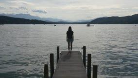 La donna pensierosa sta sul bacino di chiaro lago archivi video