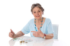 La donna pensionata conta le sue finanze - donna più anziana isolata su briciolo Fotografia Stock Libera da Diritti