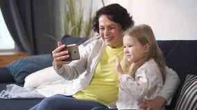 La donna pensionata e poca nipote sta parlando con la gente dalla conferenza online stock footage