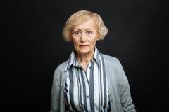 La donna pensionata risoluta che esprime la rabbia nel nero ha colorato lo studio Immagine Stock Libera da Diritti