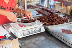 La donna pesa la carne di maiale secca cinese immagini stock