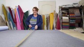 La donna più anziana in una fabbrica della mobilia sta preparando un materiale grigio per la misurazione e tagliare stock footage