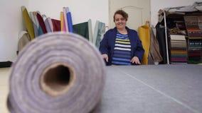 La donna più anziana in una fabbrica della mobilia sta preparando un materiale grigio per la misurazione e tagliare archivi video