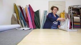 La donna più anziana in una fabbrica della mobilia sta tagliando un materiale grigio per il sofà archivi video