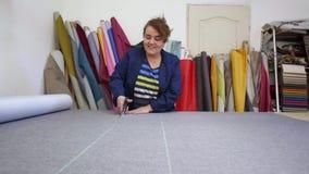 La donna più anziana in una fabbrica della mobilia sta tagliando un materiale grigio per il sofà video d archivio