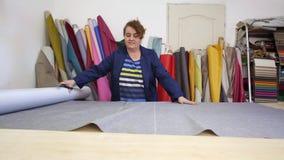 La donna più anziana in una fabbrica della mobilia sta tagliando un materiale grigio per il sofà stock footage