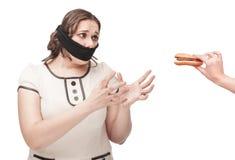 La donna più di dimensione ha imbavagliato l'allungamento delle mani all'hamburger Fotografie Stock