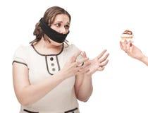 La donna più di dimensione ha imbavagliato l'allungamento delle mani alla pasticceria Immagini Stock