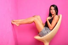 La donna a piedi nudi sorridente si siede sulla presidenza di plastica Fotografie Stock Libere da Diritti