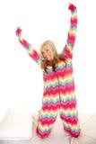 La donna in pigiami variopinti si inginocchia sull'allungamento del letto Immagine Stock Libera da Diritti