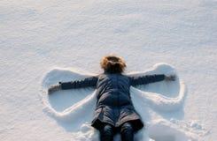 La donna in piumino blu con un cappuccio della pelliccia fa un angelo della neve fotografia stock