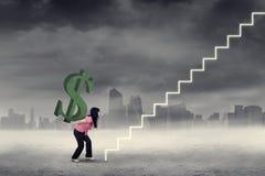 La donna porta il simbolo del dollaro sulle scala Fotografia Stock Libera da Diritti