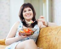 La donna positiva mangia l'insalata dei pomodori Immagini Stock Libere da Diritti