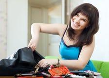 Donna positiva che trova qualche cosa in borsa Fotografie Stock Libere da Diritti