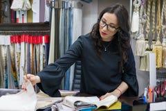 La donna possiede un deposito dei tessuti interni e la decorazione funziona con i campioni dei materiali Negozio del tessuto dell fotografie stock libere da diritti