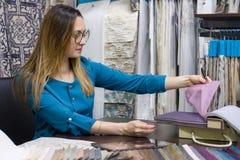 La donna possiede un deposito dei tessuti interni e la decorazione funziona con i campioni dei materiali Negozio del tessuto dell fotografia stock