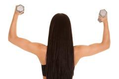 La donna posteriore di vista arma i pesi immagine stock