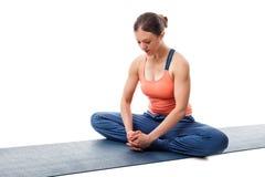 La donna pratica il konasana di Baddha di asana di yoga fotografie stock