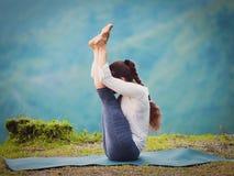 La donna pratica il paschimottanasana di mukha di Urdhva di asana di yoga Immagini Stock