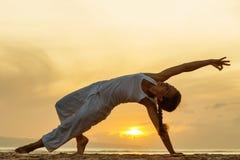 La donna pratica l'yoga alla spiaggia al tramonto su Bali in indone immagini stock libere da diritti