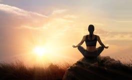 La donna pratica meditare l'yoga a è un asana su una pietra, sunse fotografie stock