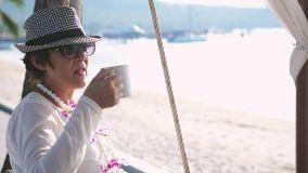 La donna premurosa nei resti invecchiati beve il caffè su oscillazione sulla bella spiaggia ed oscilla Movimento lento 3840x2160 stock footage