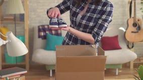 La donna prende i vestiti dei bambini dalla scatola, muoventesi verso una nuova casa stock footage