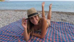 La donna prende il sole sulla spiaggia alla spiaggia, trovantesi sullo stomaco che oscilla le sue gambe stock footage