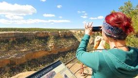 La donna prende l'immagine di Cliff Dwellings With Smartphone immagine stock