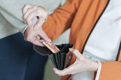 La donna prende a soldi dalla borsa dell'le donne senior Immagine Stock Libera da Diritti