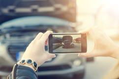 La donna prende una foto Automobile rotta su un fondo La donna si siede su una ruota riparazione della donna un'automobile Sfondo Fotografia Stock