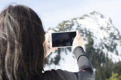 La donna, prende una foto con il cellulare, backgroung dalle montagne Fotografie Stock Libere da Diritti