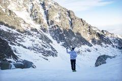 La donna, prende una foto con il cellulare, backgroung dalle montagne Immagini Stock