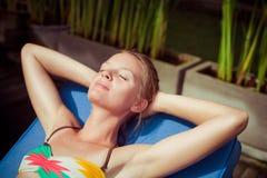 La donna prendente il sole vicino ad una piscina Immagini Stock Libere da Diritti