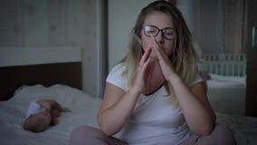 La donna preoccupata in occhiali soffre dai headachesits su fondo del bambino sul letto a casa video d archivio