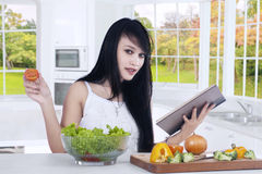 La donna prepara l'insalata mentre libro di lettura Fotografia Stock