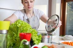 La donna prepara un pasto sano in cucina moderna Fotografia Stock