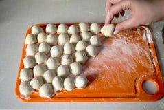 La donna produce gli gnocchi alla cucina Fotografia Stock