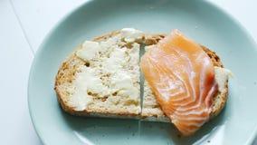 La donna produce i panini semplici del pesce per la prima colazione archivi video