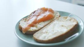 La donna produce i panini semplici del pesce per la prima colazione stock footage