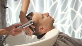 La donna professionale è con attenzione lavante e pulente la testa del giovane con la nuova acconciatura stock footage