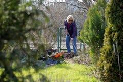 La donna pulisce il giardino in molla in anticipo Immagini Stock Libere da Diritti