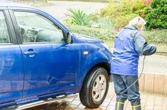 La donna pulisce manualmente l'automobile di famiglia Immagine Stock