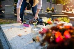 La donna pulisce una tomba fotografie stock libere da diritti