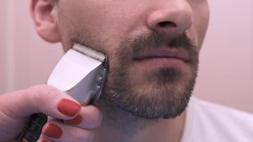 La donna rade l'uomo, rasoio elettrico del rasoio stock footage