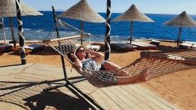 La donna raffredda nell'amaca sulla spiaggia, vacanza sul mare, rilassantesi sulla spiaggia, il mare e la ricreazione, la sabbia  video d archivio