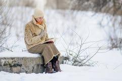 La donna ready un libro nell'inverno Fotografie Stock Libere da Diritti