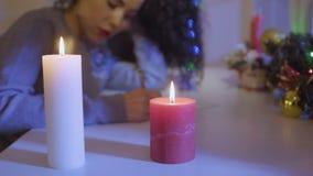 La donna redige una lista di obiettivi alla tavola decorata con gli attributi di Natale stock footage