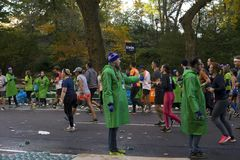 La donna regge fuori ai corridori che partecipano alla maratona di NYC immagine stock