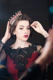 La donna, regina con la corona, guarda in specchio Lusso, modo Fotografie Stock
